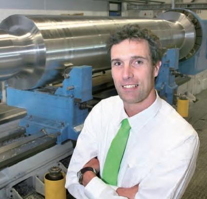 """Jakom-directeur Hessel Hendriks: """"De opleidingstijd is sterk teruggebracht, met inzet van speciale productieautomatisering"""". Op de achtergrond een 34-tons as voor de baggerindustrie."""